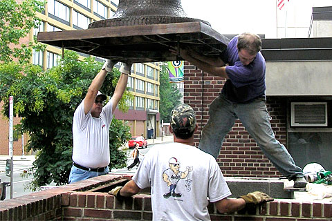 Sculptor James Peniston, right, guides the sculpture into place. 'Keys To Community,' a nine-foot bronze bust of Ben Franklin for downtown Philadelphia